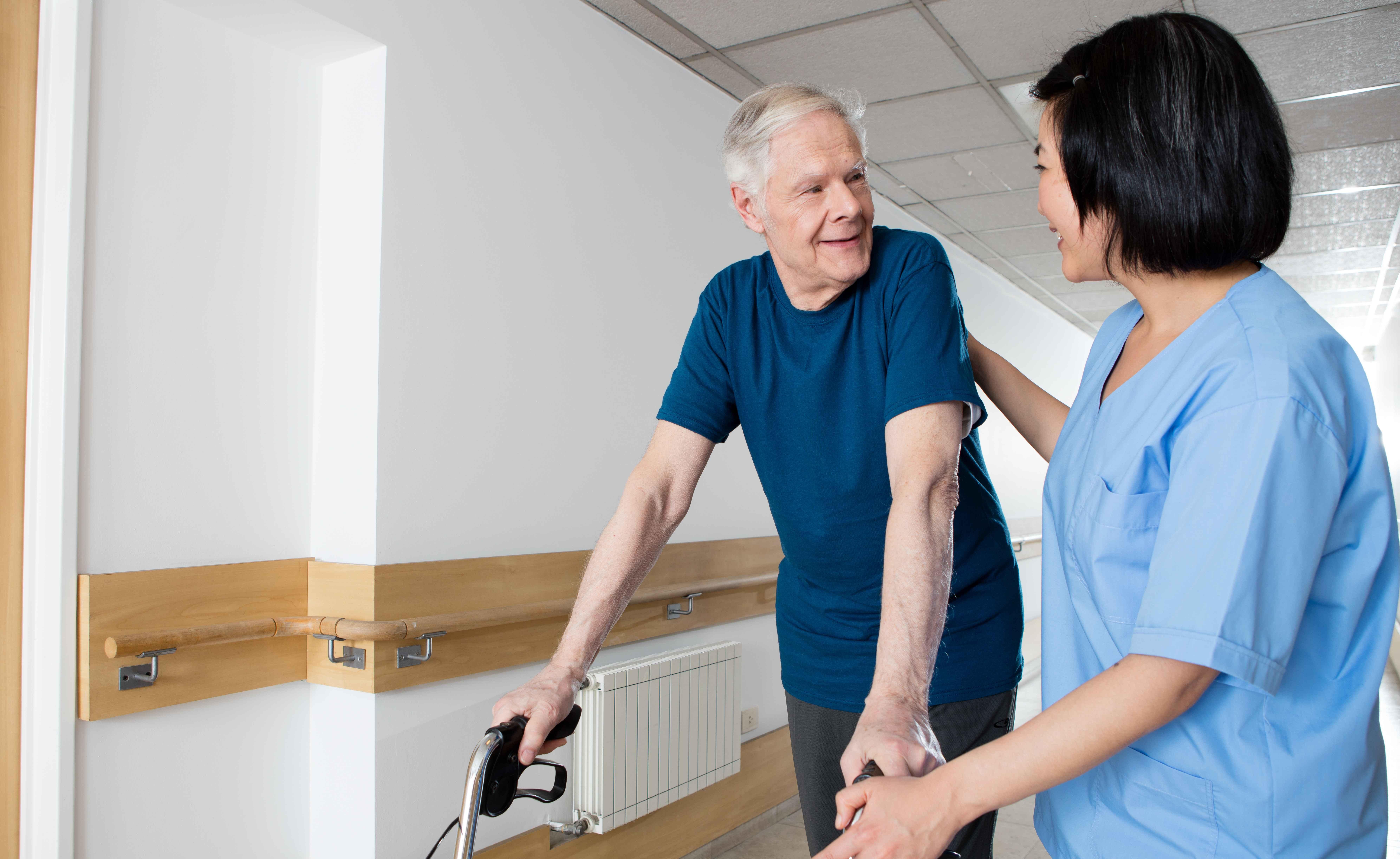 Older man walking through a hallway using a Zimmer frame. Nurse in uniform helping him