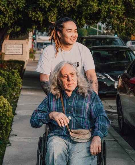 Person in a blue checked shirt sitting in a wheelchair, being pushed by a younger person