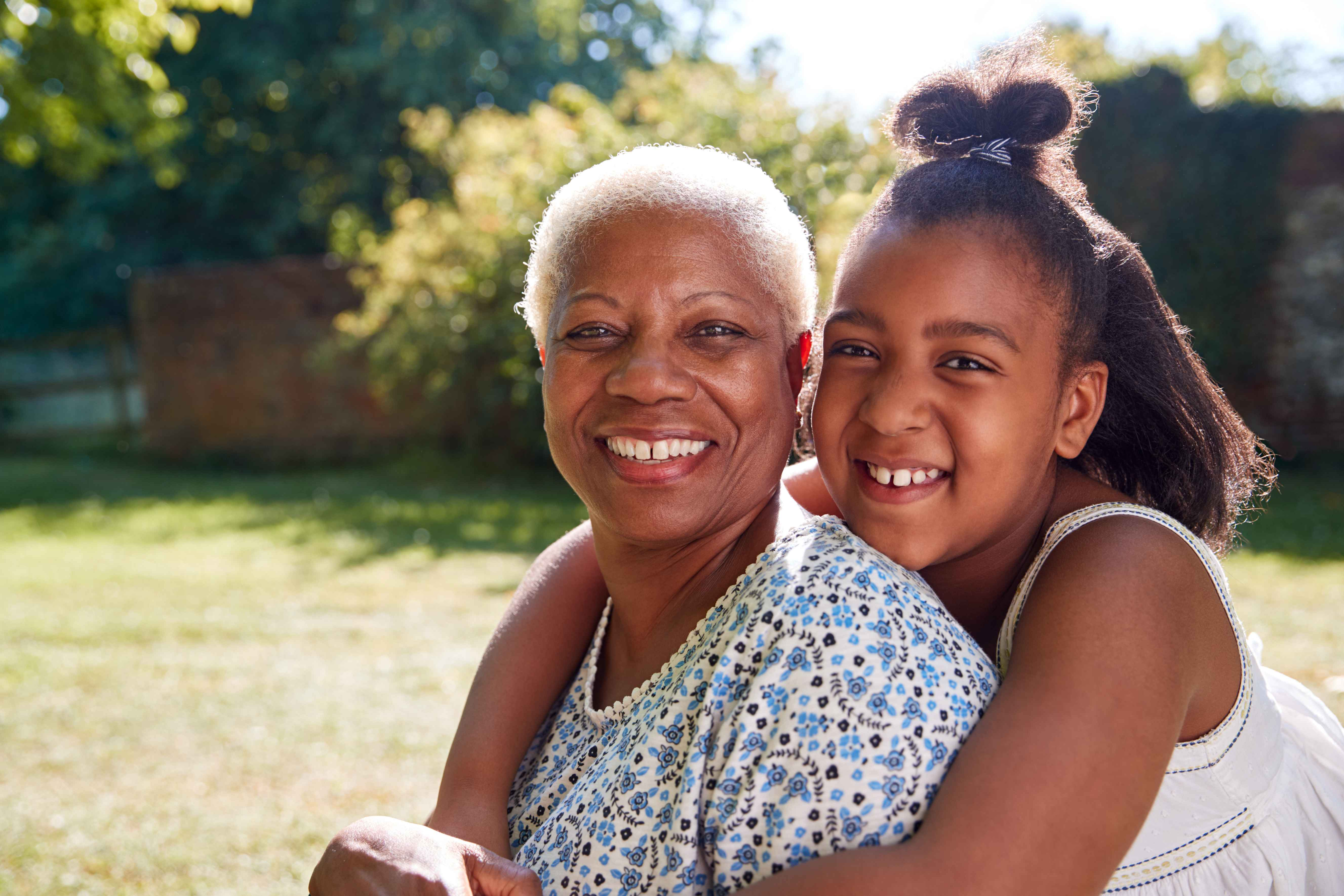 Older Black woman with a young granddaughter smiling in the sun