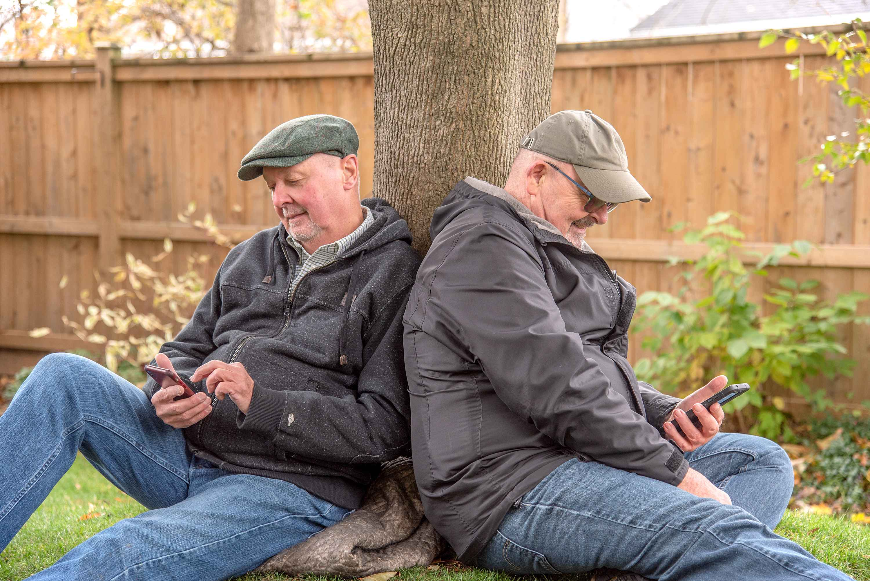 Older married gay couple leaning against a tree looking at their phones and smiling