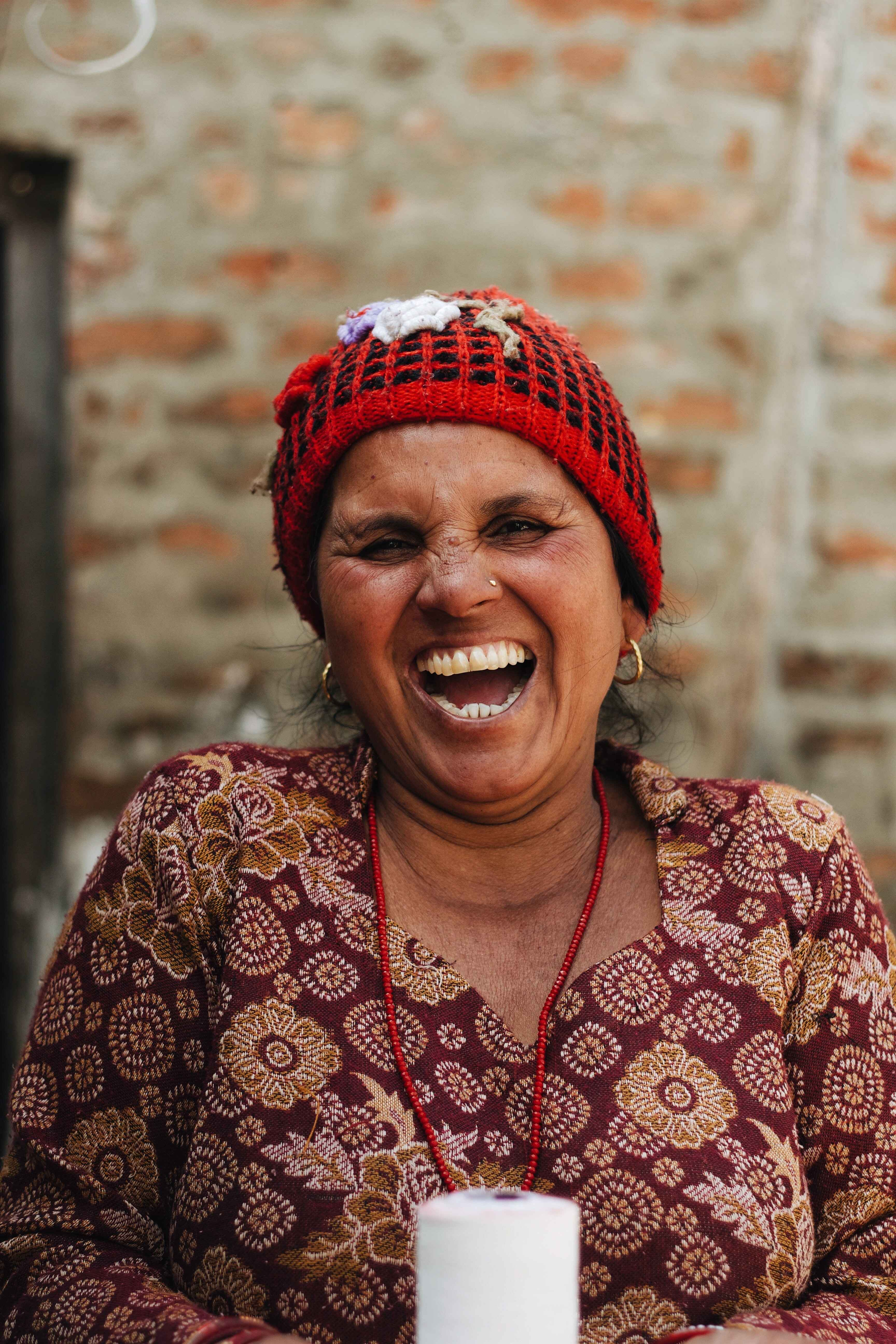 Image of an Asian woman smiling with her eyes closed wearing a red head wrap